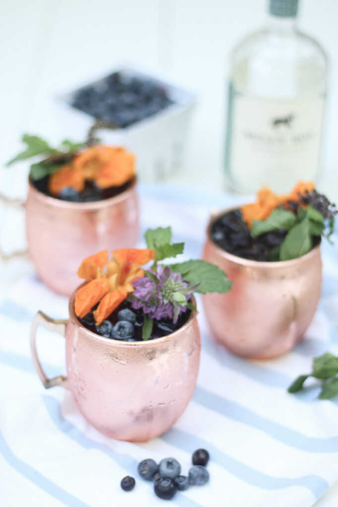 Blueberry Gin Mule with edible flowers