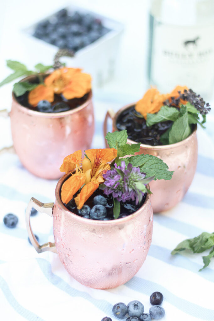 Blueberry Gin Mule with blueberries and bottle of gin